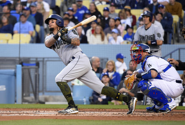 San Diego Padres' Freddy Galvis, left, hits a two-run home run as Los Angeles Dodgers catcher Yasmani Grandal watches during the second inning of a baseball game Saturday, May 26, 2018, in Los Angeles. (AP Photo/Mark J. Terrill)