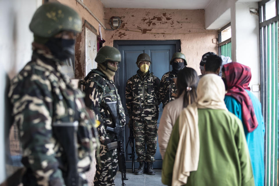 Soldiers stand guard as Kashmiris wait outside a polling booth to cast their votes during the first phase of District Development Councils election on the outskirts of Srinagar, Indian controlled Kashmir, Saturday, Nov. 28, 2020. Thousands of people in Indian-controlled Kashmir voted Saturday amid tight security and freezing cold temperatures in the first phase of local elections, the first since New Delhi revoked the disputed region's semiautonomous status. (AP Photo/Mukhtar Khan)
