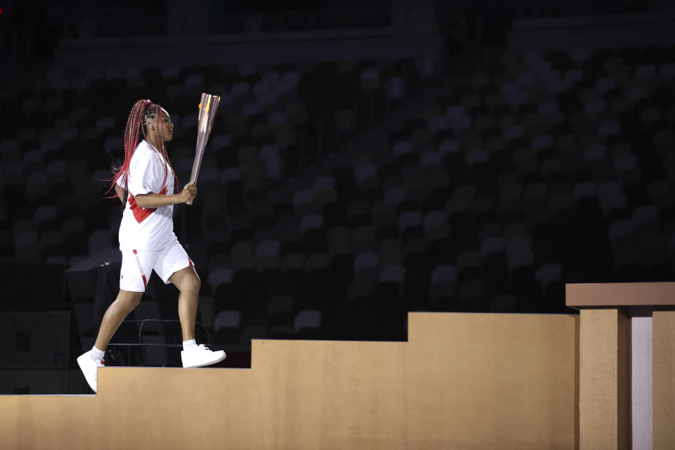 <p>Naomi Osaka carries the Olympic Torch during the opening ceremony in the Olympic Stadium at the 2020 Summer Olympics, Friday, July 23, 2021, in Tokyo, Japan. (Hannah McKay/Pool Photo via AP)</p>