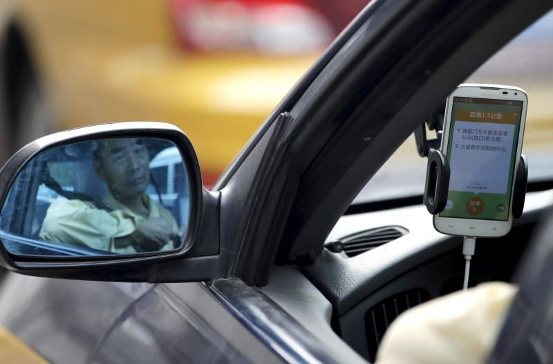 A taxi driver is reflected on a side mirror as he uses Didi Chuxing car-hailing application in Beijing