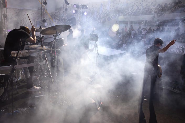 """Israeli musician Ivri Lider perform in front of audience during a performance where all guests were required to show """"green passport"""" proof of receiving a COVID-19 vaccination or full recovery from the virus at a soccer stadium in Tel Aviv, Friday, March. 5, 2021. (AP Photo/Oded Balilty)"""