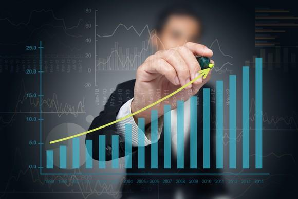 A man drawing a rising line over a bar chart that heads higher