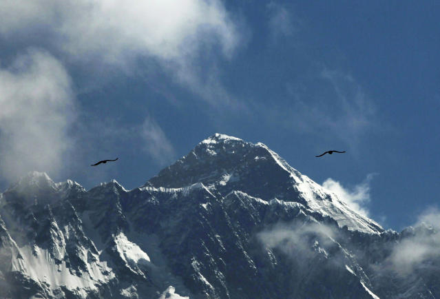 FILE - In this May 27, 2019, file photo, birds fly as Mount Everest is seen from Namche Bajar, Solukhumbu district, Nepal. Five climbers are attempting to scale Mount Everest, battling extreme cold, high winds and piled-up snow and ice as they try to become the first to reach the top of the world's highest mountain in the winter in 27 years, an official said Wednesday, Jan. 15, 2020. (AP Photo/Niranjan Shrestha, File)