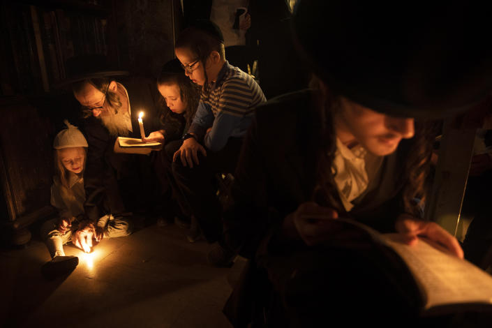 Ultra-Orthodox Jewish men and children read by candlelight from the book of Eicha (Book of Lamentations) during the annual Tisha B'Av (Ninth of Av) fasting and memorial day, commemorating the destruction of ancient Jerusalem temples, in the Ultra-Orthodox neighborhood of Mea Shearim in Jerusalem, Saturday, July 17, 2021. (AP Photo/Oded Balilty)