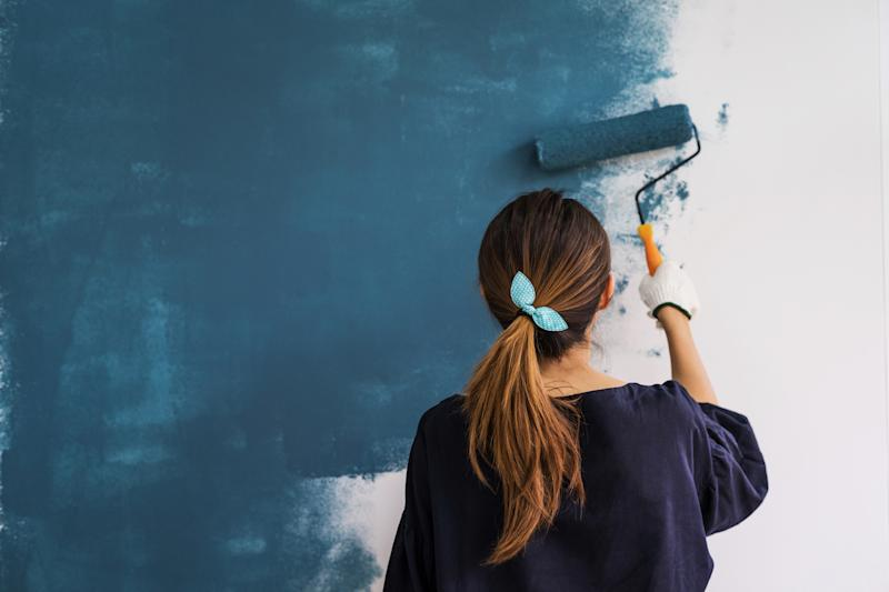 Woman painting a room blue with a paint roller.