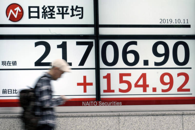A man walks past an electronic stock board showing Japan's Nikkei 225 index at a securities firm in Tokyo Friday, Oct. 11, 2019. Asian stock markets followed Wall Street higher Friday on optimism about U.S.-Chinese talks on ending a tariff war.(AP Photo/Eugene Hoshiko)