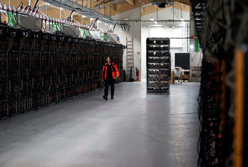 In this photo taken on January 17, 2018, inside the Genesis Mining cryptocurrency mine in Iceland, a man walks along a row of computer rigs that run around the clock 'mining' bitcoin. At the edge of the Arctic, bitcoin miners seek natural cooling and competitive prices for Iceland's abundance of renewable energy. (AP Photos/Egill Bjarnason)