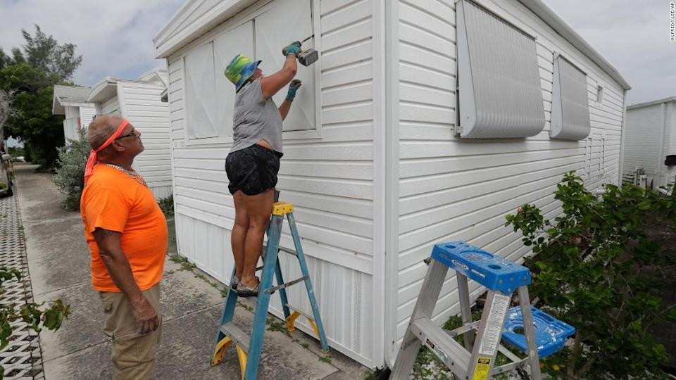 """<p>Chris Nagiewicz watches as his wife Mary attaches a hurricane panel on a trailer home in Briny Breezes, Florida, on Saturday, August 1. </p><div class=""""cnn--image__credit""""><em><small>Credit: Wilfredo Lee/AP / Associated Press</small></em></div>"""