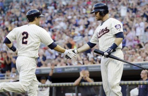 Minnesota Twins' Ryan Doumit, right, congratulates teammate Brian Dozier who scores on an RBI-double by Joe Mauer off New York Yankees pitcher CC Sabathia in the third inning of a baseball game on Wednesday, July 3, 2013, in Minneapolis. (AP Photo/Jim Mone)