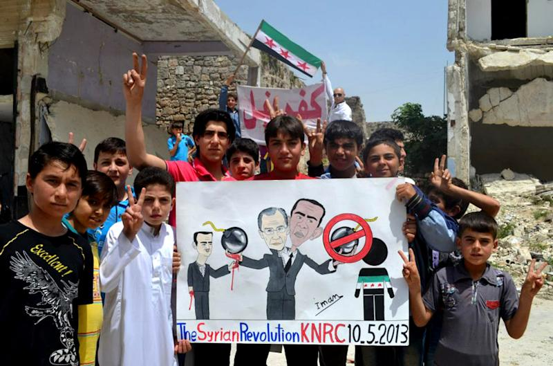 """In this citizen journalism image provided by Edlib News Network, ENN, which has been authenticated based on its contents and other AP reporting, anti-Syrian regime protesters hold a poster depcting Syrian President Bashar Assad, left, Russian Foreign Minister Sergei Lavrov, center, and U.S. President Barack Obama, right during a demonstration, at Kafr Nabil town, in Idlib province, northern Syria, Friday May 10, 2013. Arabic on the banner background reads, """"Kafr Nabil."""" (AP Photo/Edlib News Network ENN)"""