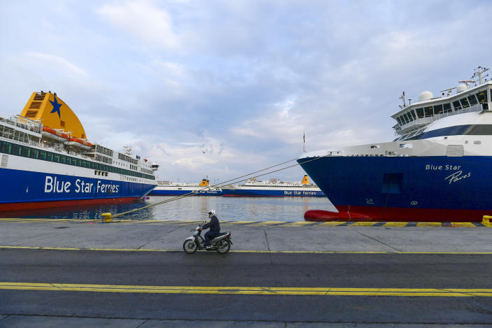 A man rides his motorcycle during a 24-hour labour strike at the port of Piraeus, near Athens, Thursday, June 10, 2021. Greece's biggest labor unions stage a 24-hour strike to protest a draft labor bill being debated in parliament, which workers say will erode their rights. (AP Photo/Michael Varaklas)
