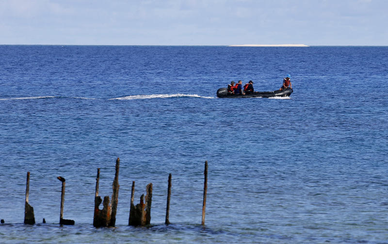 FILE - In this April 21, 2017, photo, engineers from NAMRIA, the central mapping agency of the Philippine Government, survey the area around the Philippine-claimed Thitu Island with a sandbar sitting on the horizon off the disputed South China Sea in western Philippines. Ships from the Chinese navy and coast guard along with fishing boats from its maritime militia have been deployed to keep watch on Philippine development work on the island of Thitu. (AP Photo/Bullit Marquez, File)