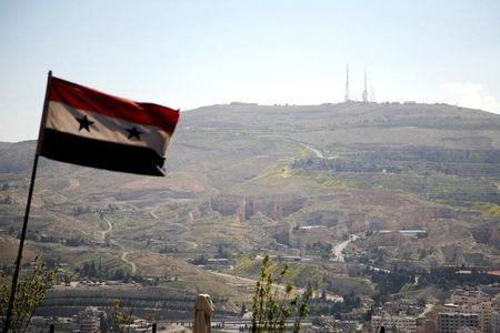 A Syrian national flag flutters as Qasioun mountain is seen in the background from Damascus