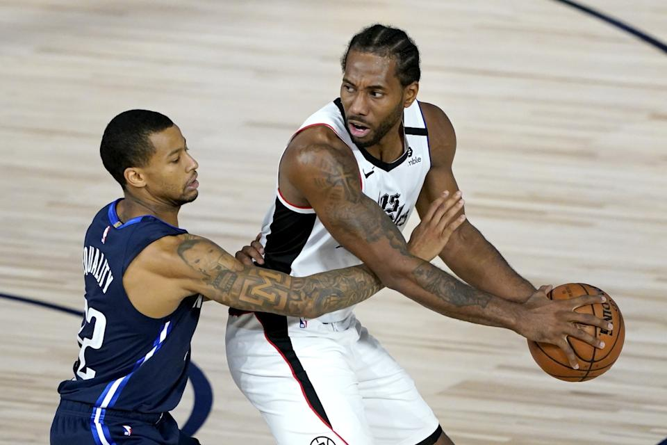 Clippers' Kawhi Leonard is guarded by Dallas Mavericks' Trey Burke.
