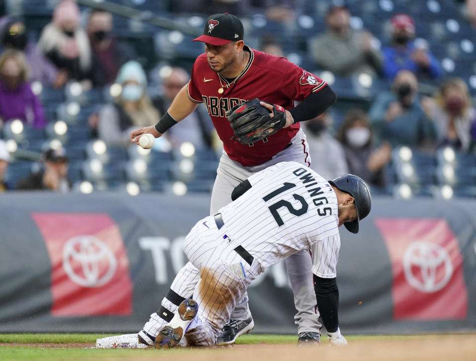 Colorado Rockies' Chris Owings, front, slides safely into third base with an RBI triple as Arizona Diamondbacks third baseman Asdrubal Cabrera fields the throw during the first inning of a baseball game Wednesday, April 7, 2021, in Denver. (AP Photo/David Zalubowski)