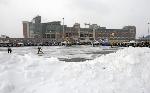 Fans tailgate outside a snowy Lambeau Field before an NFL football game between the Green Bay Packers and the Pittsburgh Steelers Sunday, Dec. 22, 2013, in Green Bay, Wis. (AP Photo/Mike Roemer)
