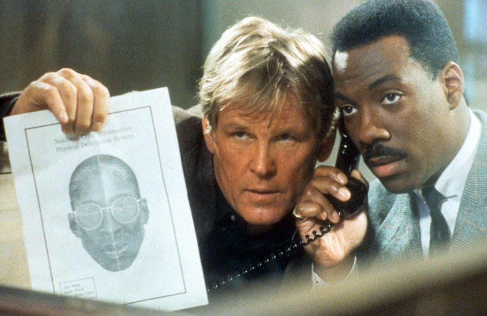 Nick Nolte and Eddie Murphy listening to phone while showing artist's depiction of suspect in scene from the film 'Another 48 Hrs.', 1990. (Photo by Paramount/Getty Images)