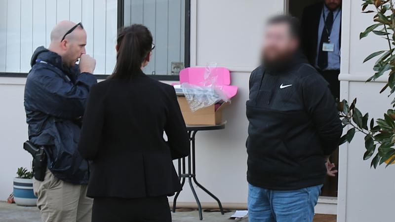 Two NSW Police detectives standing with handcuffed fake tax agent.