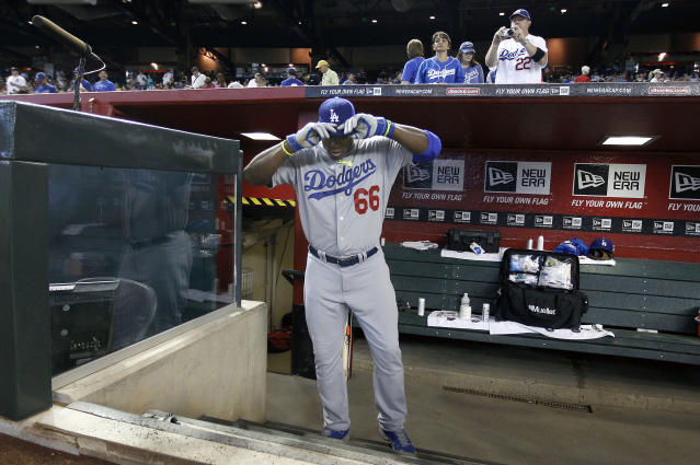 Los Angeles Dodgers' Yasiel Puig adjust his cap before taking the field at the start of a baseball game against the Arizona Diamondbacks, Sunday, April 13, 2014, in Phoenix. (AP Photo/Ralph Freso)