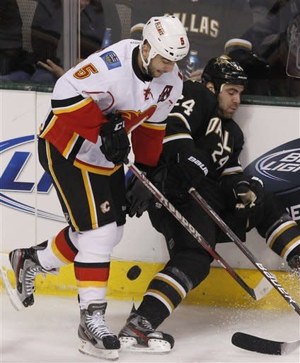 Calgary Flames defenseman Mark Giordano (5) and Dallas Stars left wing Eric Nystrom (24) try to get control of the puck during the first period of an NHL hockey game in Dallas, Saturday, March 24, 2012. (AP Photo/LM Otero)