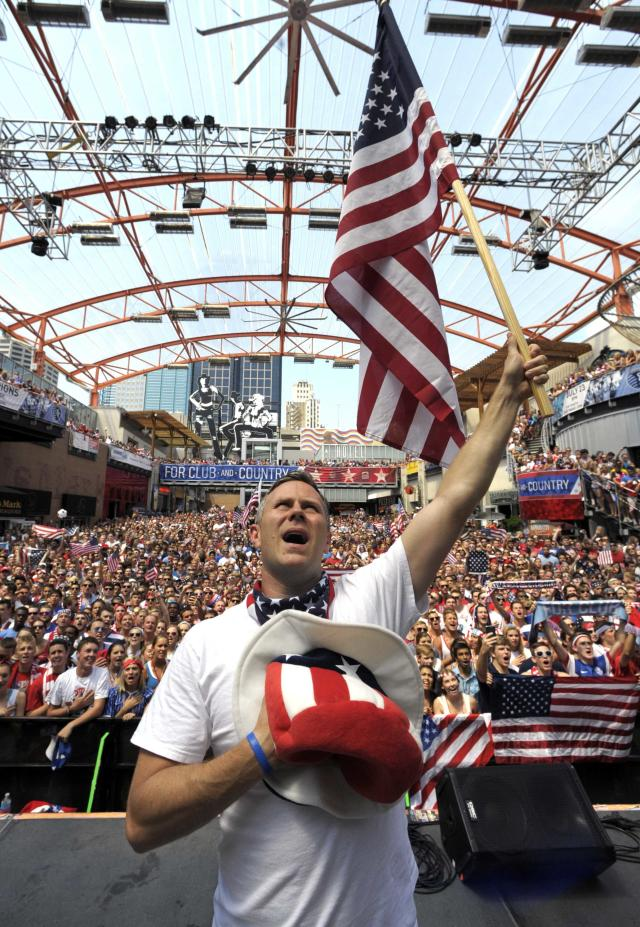 Sports radio DJ Nate Bukaty leads the crowd in the national anthem as they watch a World Cup round of 16 soccer match between Belgium and the U.S. In Brazil, on a large television screen in the Power & Light District in downtown Kansas City, Missouri July 1, 2014. REUTERS/Dave Kaup (UNITED STATES - Tags: SPORT SOCCER WORLD CUP ENTERTAINMENT)