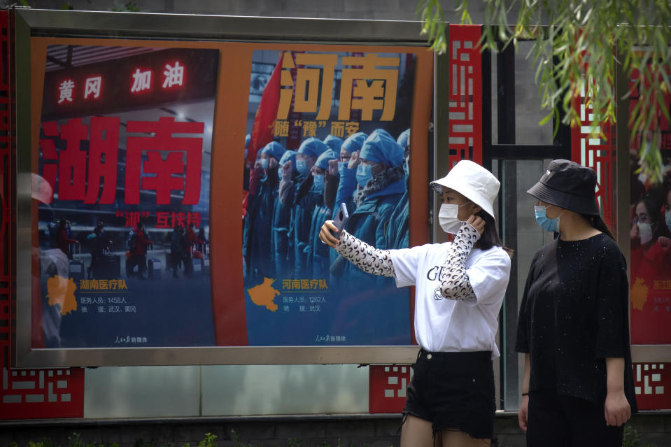 People wearing face masks to protect against the new coronavirus take photos near billboards honoring medical workers who responded to the coronavirus outbreak in Wuhan at a public park in Beijing, Friday, June 26, 2020. China reported a further decline in new cases Friday with about a dozen mostly in Beijing, where mass testing has been done following an outbreak that appears to have been largely brought under control. (AP Photo/Mark Schiefelbein)