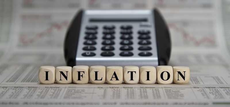 Blocks spelling out inflation sitting in front of a calculator.