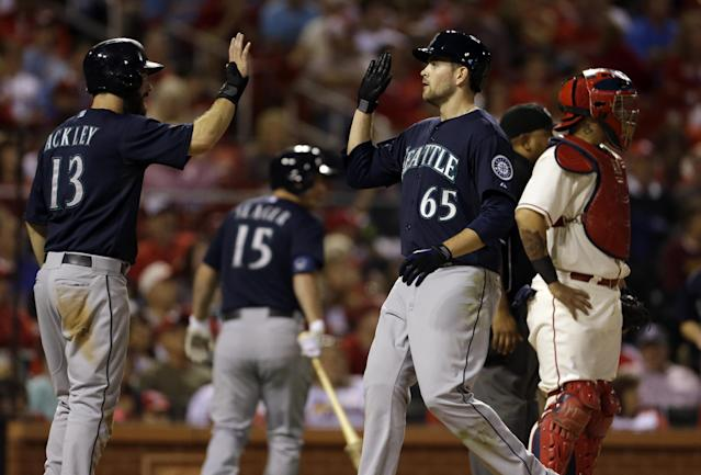 Seattle Mariners' Dustin Ackley (13) and James Paxton (65) celebrate after scoring on a two-run double by Franklin Gutierrez as St. Louis Cardinals catcher Yadier Molina, right, stands by during the fifth inning of a baseball game, Saturday, Sept. 14, 2013, in St. Louis. (AP Photo/Jeff Roberson)