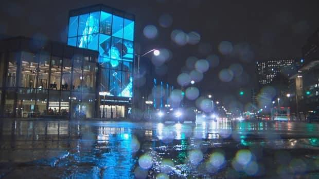 Nighttime rain falls near the National Arts Centre in Ottawa as most of our area is under a rainfall warning. Ontario's vaccine passport system begins and the NAC is included. (CBC - image credit)