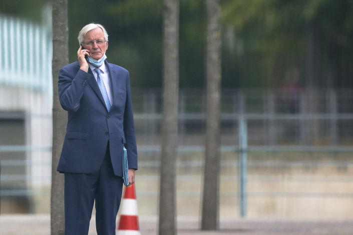Chief EU negotiator Michel Barnier makes a phone call as he leaves the chancellery following a meeting with German Chancellor Angela Merkel in Berlin, Germany, Monday, Oct. 5, 2020. (AP Photo/Markus Schreiber)