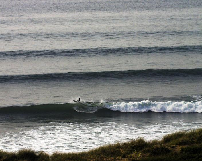 Lines of waves out to sea with a surfer in the foreground.