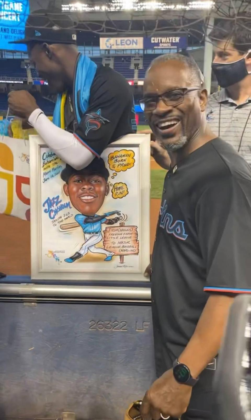 """Bahamas Minister of Youth, Sports and Culture Iram Lewis presented a caricature painting to shortstop Jasrado """"Jazz"""" Prince Hermis Arrington Chisholm Jr., a star rookie for the Marlins."""