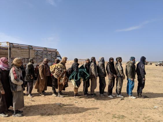 Men who fled the last Isis-held area of Syria line up to be questioned by US and Kurdish officials(Richard Hall)