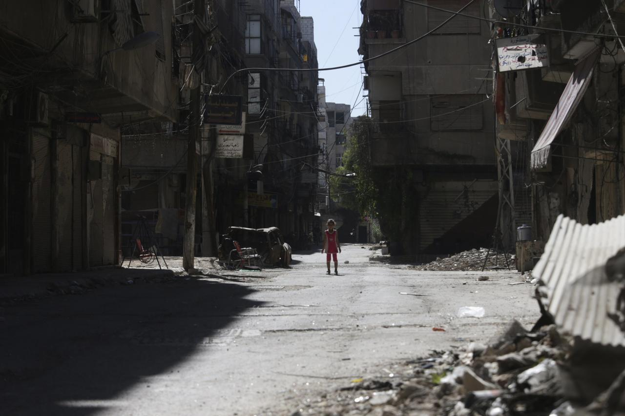 A girl stands in a damaged street in Ain Tarma, in Eastern Ghouta, a suburb of Damascus August 21, 2014. A year passed since the chemical attacks on Eastern Ghouta of Damascus. REUTERS/Bassam Khabieh (SYRIA - Tags: POLITICS CIVIL UNREST CONFLICT TPX IMAGES OF THE DAY)