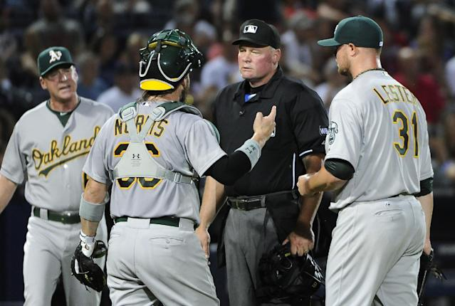 Oakland Athletics catcher Derek Norris (36), pitcher Jon Lester (31) and manager Bob Melvin plead their case to umpire Ted Barrett after an infield line drive and error allowed Atlanta Braves' Justin Upton to advance from first base to third base during the second inning of a baseball game Sunday, Aug. 17, 2014, in Atlanta. (AP Photo/David Tulis)