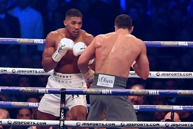 Britain's Anthony Joshua (L) looks for an opening against Ukraine's Wladimir Klitschko during the third round of their IBF, IBO and WBA, world heavyweight title fight, at Wembley Stadium in London, on April 29, 2017
