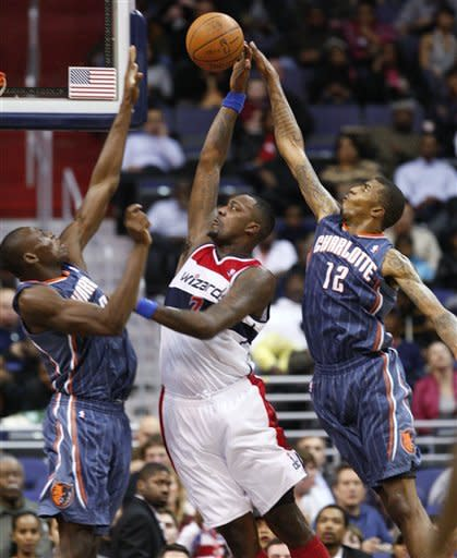 Charlotte Bobcats forward Tyrus Thomas (12) swats away a shot attempt by Washington Wizards forward Andray Blatche (7) as Bobcats center Bismack Biyomb, left, defends during the second quarter of an NBA basketball game in Washington, Wednesday, Jan. 25, 2012. (AP Photo/Ann Heisenfelt)