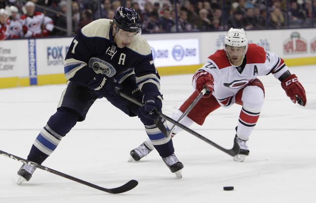 Columbus Blue Jackets' Jack Johnson, left, tries to shoot the puck as Carolina Hurricanes' Manny Malhotra defends during the second period of an NHL hockey game on Friday, Jan. 10, 2014, in Columbus, Ohio. (AP Photo/Jay LaPrete)
