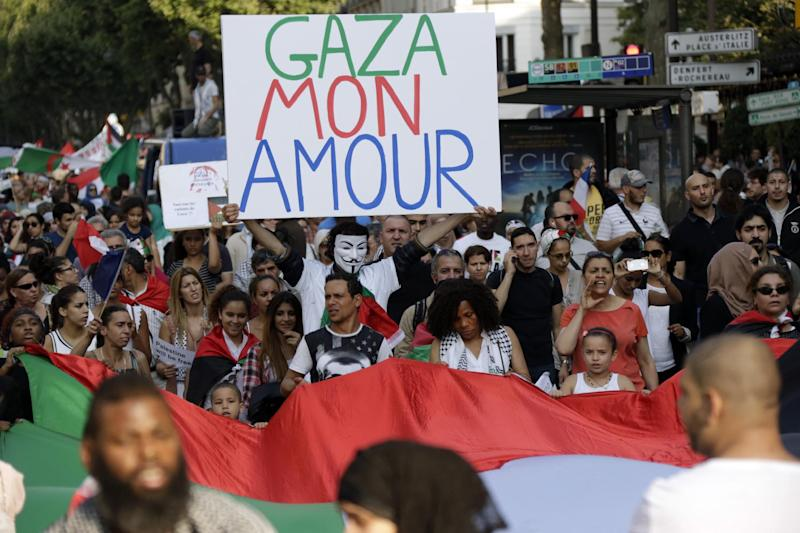 "A protester wearing a Guy Fawkes mask hold a sign reading ""Gaza my love"" as others carry Palestinian flags during a demonstration in Paris to denounce Israel's military campaign in Gaza on July 23, 2014 (AFP Photo/Kenzo Tribouillard)"