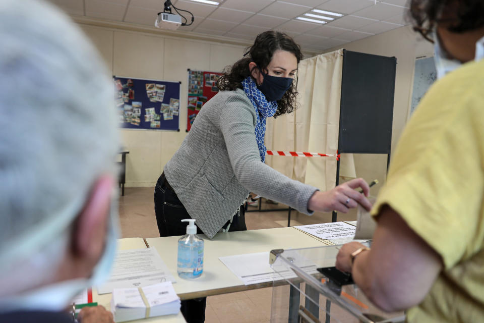 A woman casts a vote at a voting center during the second round of the municipal elections, in Rennes, western France, Sunday, June 28, 2020. France is holding the second round of municipal elections in 5,000 towns and cities Sunday that got postponed due to the country's coronavirus outbreak. (AP Photo/David Vincent)