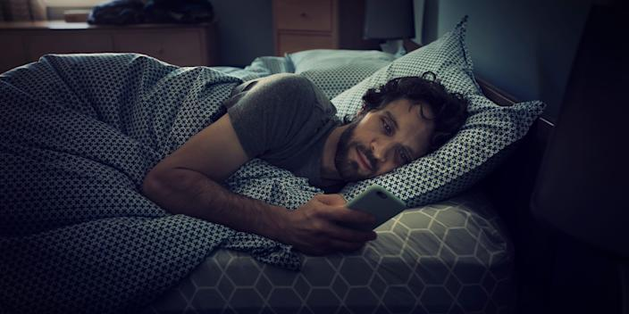 man laying in bed looking at phone scrolling texting
