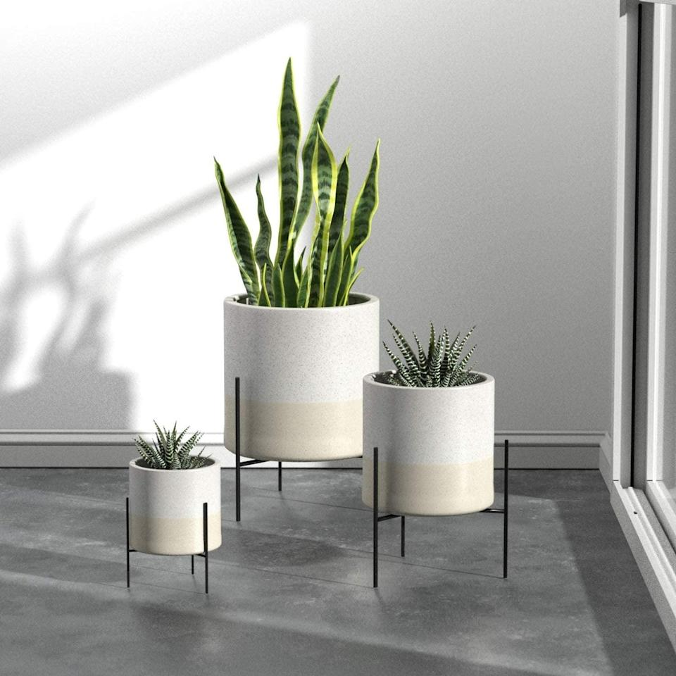 <p>This <span>Rivet Mid-Century Ceramic Planter with Stand</span> ($82) comes in various sizes and colors.</p>