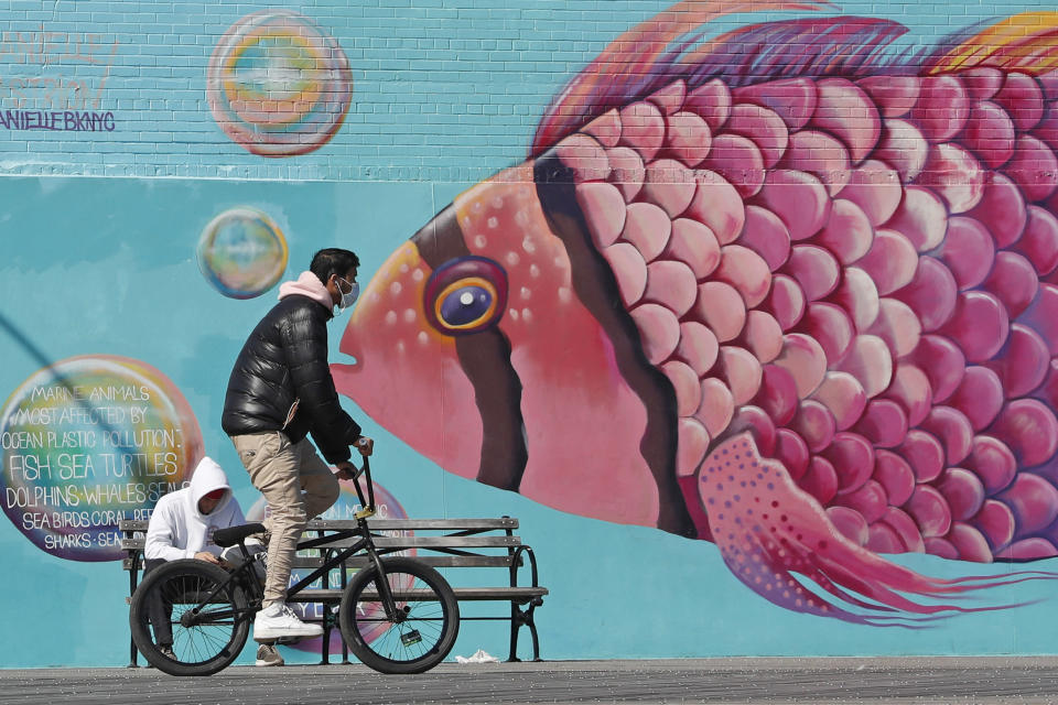 FILE - In this April 2, 2020, file photo, a face-mask wearing cyclist pedals past a mural of a tropical fish on the Coney Island boardwalk in the Brooklyn borough of New York. From Cape Cod to California, festivals are being canceled, businesses in tourist havens are looking at empty reservation books, and people who have been cooped up through a dismal spring are worrying summer will bring just more of the same. (AP Photo/Kathy Willens, File)