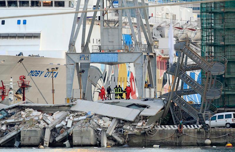 Rescue personnel stand on rubble next to a tilted staircase, part of a control tower which collapsed after a cargo ship slammed into it during a shift change Tuesday night in the port of Genoa, northern Italy, killing at least three people, Wednesday, May 8, 2013. Four others were hospitalized and a half-dozen people remained unaccounted for, including some feared trapped inside the submerged elevator of the control tower, officials said. By Wednesday morning, all that was left of the control tower was the mangled exterior staircase, tilted to its side. The tower itself, which was located on the very edge of a dock jutting out into the harbor, was either in the water or in a heap of wreckage on the dock.  (AP Photo/Francesco Pecoraro)