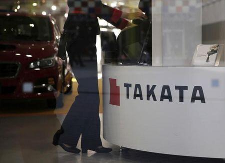 FILE PHOTO: A woman stands next to a logo of Takata Corp at a showroom for vehicles in Tokyo