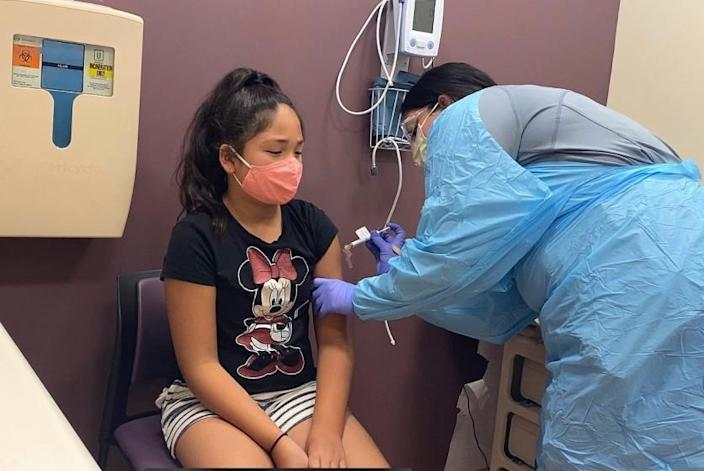 Luci Guardino, 11, receives her first dose of a COVID-19 vaccine as part of a recently launched trial at Kaiser Permanente sites in Sacramento, Oakland and Santa Clara.