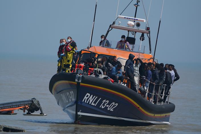 A salvage tractor ashore tows the Dungeness lifeboat to the beach after its return carrying people suspected of being migrants from France, recovered following an incident with a small boat in the English Channel.  Photo date: Tuesday, July 20, 2021.