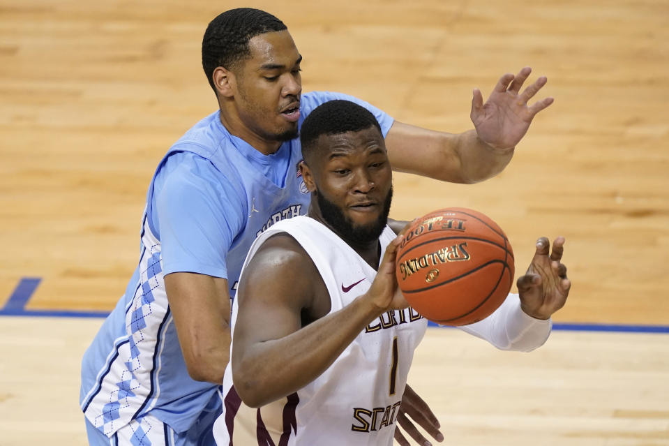 Florida State forward RaiQuan Gray (1) looks to pass the ball as North Carolina forward Garrison Brooks, left, defends during the first half of an NCAA college basketball game in the semifinal round of the Atlantic Coast Conference tournament in Greensboro, N.C., Friday, March 12, 2021. (AP Photo/Gerry Broome)