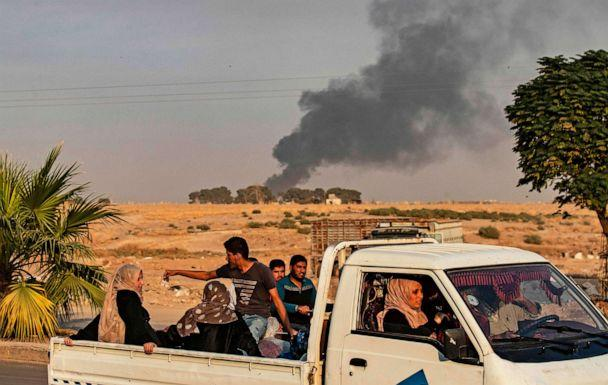 PHOTO: Civilians ride a pickup truck as smoke billows following Turkish bombardment in the northeastern town of Ras al-Ain in Syria's Hasakeh province along the Turkish border on Oct. 9, 2019. (Delil Souleiman/AFP via Getty Images, FILE)