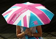 A woman holds a London 2012 branded umbrella at the launch of the London Olympic Games official merchandise on July 30, 2010 in London, England. (Photo by Oli Scarff/Getty Images)